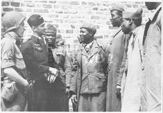 French colonial troops from a famous Senegalese regiment, who were captured by the Germans in 1940 and forced to work in labor details, chat with a French officer and an American sergeant soon after their escape to the American lines in Normandy. They said they wanted to join Allied forces and carry on the fight against the Germans.