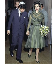 May when Elizabeth Taylor married her fourth husband, singer Eddie Fisher - who left his wife Debbie Reynolds to marry Taylor – she wore a short, hooded, forest green dress with matching shoes and a bouquet made up of orchids and baby's breath Famous Wedding Dresses, Green Wedding Dresses, Celebrity Wedding Dresses, Wedding Dress Pictures, Celebrity Weddings, Wedding Gowns, Wedding Fair, Wedding Album, Wedding Photos