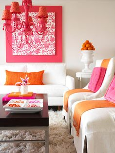 Color Speaks Volumes    In this all-white room, vibrant orange and pink accents create a fashionable living space.  Why It Works   -- Bold complementary colors against white walls and furniture grab attention.   -- A wrapped canvas in a bold pink pattern makes for easy artwork in the simple room.   -- The room's perfect symmetry is calming and chic