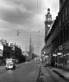 The view looking east along Great Western Road, early one morning in 1955. In the distance are the spires of Lansdowne Parish Church and (behind it) of St Mary's Episcopal Cathedral. The distinctive clock tower of Cooper & Co's grocery store and offices on the corner of Bank Street is on the right. The roadway is formed of granite setts. - TheGlasgowStory