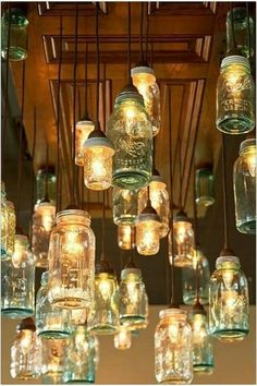 Dinning/Kitchen Area: I like this idea to give WAY more lighting to dark room! Could Wine or Soda Bottles along with Mason Jars. A whole page of jar lights, love that this picture has them hanging from an old door! Mason Jar Chandelier, Mason Jar Lighting, Mason Jar Lamp, Kitchen Lighting, Diy Chandelier, Pot Mason Diy, Mason Jar Crafts, Unique Lighting, Outdoor Lighting