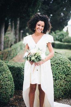 A modern bride wears a short-sleeved v-neck hi-lo wedding dress.
