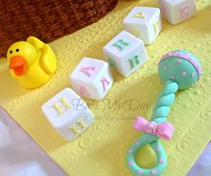 3D baby bassinet cake, with fondant bib, blanket, bows and sugar rubber ducky, blocks, rattle, booties and bottle.