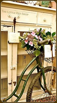 "very cute- love the use of metal screen for the cabinet doors and the ""little red shop"" on the drawer, the old bike is great too"
