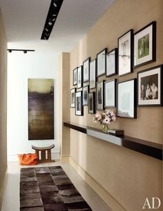 In keeping with the aesthetics of this hallway in the Manhattan home of actress Julianna Margulies, the black-and-white family pictures are first given breathing room with clean white mats, then warmed up with dark wood frames. The gallery-style arrangement, usually prone to visual inconsistency, is unified by a single ledge shelf below, accented with soft pink flowers.