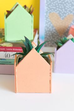 Make a colorful pastel set of DIY mini house planters with plywood that slide neatly over an existing small potted plant to create a cute piece of home decor for spring! Mini Vasos, Pastel House, Small Potted Plants, E Design, Diy And Crafts, Planters, Gift Wrapping, Ideias Diy, Create