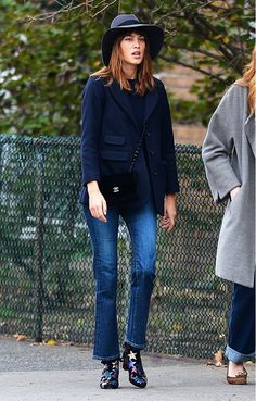 Alexa Chung wears a blue short coat, jeans, a Chanel bag, star-print boots, and a fedora