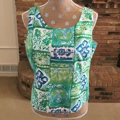 "Talbots top w/ buttons in back Cheerful print shell style top in shades of green and blue with white space. 6 white buttons down back. Vertical seams in front and back that curve towards side seams. Measures 20"" from armpit across, length is 20"". 100% cotton with 100% acetate white lining. Dry clean. Made in USA of imported fabric. Perfect for white capris or skinny jeans, straight leg slacks. Can be worn under jacket or sweater too. Gently pre-loved. Talbots Tops Blouses"