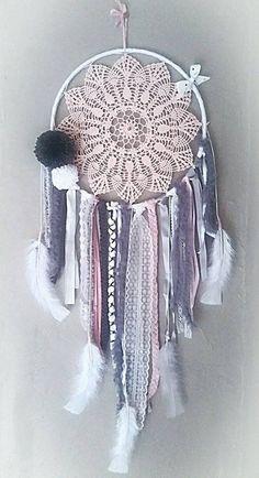 Attrape rêve de 25 cm de diamètre. 72 centimètres de longueur. Napperon rose fait main. Petite perle argentée au centre du napperon. L'attrape rêve est composé d'une diversité de laine, dentelle, rubans, plumes, fil peluche... de couleur rose, gris et blanc. Orné d'un petit nœud blanc à poids noirs et de deux pompons blanc et gris. Pièce unique. Si demande particulière pour la création d'un attrape rêve personnalisé, me contacter.