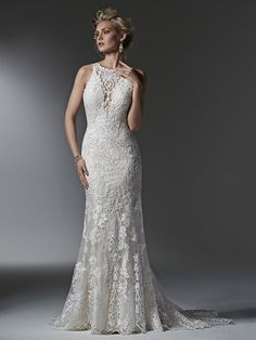 Sottero & Midgley -  Winifred Timeless and elegant, this lace sheath wedding dress features a modern illusion deep V halter neckline, a stunning, scalloped plunging back, and illusion straps. Finished with covered buttons over zipper closure.
