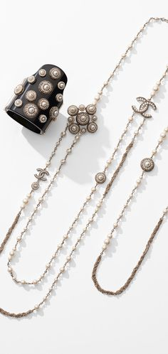 """#Fashion Jewelry.  #CHANEL long #cuff in resin, glass #pearls and CHANEL long #Necklace with glass pearls and signature CC.  Great for layering to achieve that """"more is more"""" look.  We also like this one worn alone with a black fitted turtle neck or a low cut blouse."""