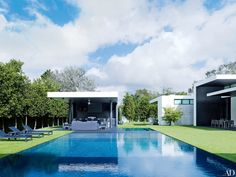 These Modern Pools Make a Minimalist Splash Photos | Architectural Digest [At baseball star Alex Rodriguez's home in Coral Gables, Florida, RH chaise longues face the wet-edge pool, while James Perse furniture occupies the adjacent barbecue cabana. Architecture firm Choeff Levy Fischman designed the residence, Briggs Edward Solomon handled the decoration, and Christopher Cawley Landscape Architecture helped revamp the grounds; the property was fitted with artificial grass to conserve water.]