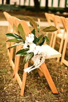 Aisle markers made with magnolia leaves and cotton branches, tied together with a light burlap ribbon. Perfect accents for an outside, southern wedding ceremony, in New Orleans.
