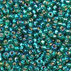 Miyuki 11/0 (2mm) Silver-Lined Emerald AB round rocaille glass seed beads, colour number 1017. Transparent blue-ish green outside, shiny inside, with an iris rainbow finish. UK seller.