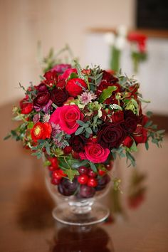 red and white flower arrangements in a compote bowl filled with mouth-watering cherries and luscious plums