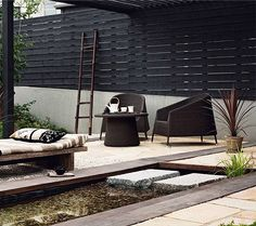 """Japanese style via Studio G.  Like the black stained fence with becomes roof, the day bed and orthogonal """"stream""""."""