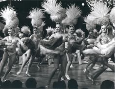 """Showgirls with feather boas and headpieces performing onstage for the show """"Lido de Paris"""" at the Stardust Resort and Casino in Las Vegas, circa 1978.  Part of the UNLV Libraries """"Showgirls"""" digital collection.  #UNLV"""