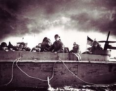 """A U.S. Coast Guard coxswain """"Jim"""" is at the helm of an LCVP carrying troops from the 4th Infantry Division toward Utah Beach on D-Day. Two M1919A4 .30-caliber Machine Guns can be seen mounted in the gun tubs at the stern of the landing craft. Today on the blog; The Americans on D-Day: A Photographic History of the Normandy Invasion. #WW2 #dday"""