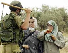 A US Israel occupation soldier threatening to beat two Palestinian women in Az Zawiya village in the West Bank.  The women are protesting against the uprooting of olive trees by US Israel bulldozers.