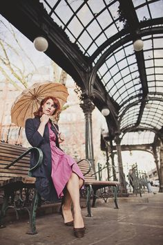 woman under the pergola in seattle wearing a galliano dress and holding a vintage umbrella
