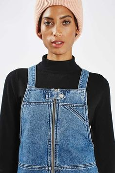 Give denim a cool spin in this MOTO utility style pinafore dress. A boxy silhouette cut with a square neckline and deep patch pockets to the front. Team it with a simple tee to finish the look. #Topshop