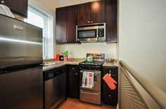 This modern kitchen has granite countertops, stainless steel appliances, and dark wood cabinets. #bjbproperties #chicagoapartments #lakeviewapartments