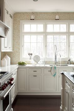 warm-toned tiled walls in white kitchen, wood floor