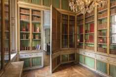 The Versailles You've Never Seen - Quintessence Marie Antoinette's library, with an intricately decorated jib door and bookcases displaying leather bound volumes embossed with her coat of arms.