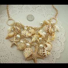 Gold, shells, pearls and crystals necklace. Shells, gold, pearls and crystals all make up this gorgeous necklace.  Very soft muted beige tones make up the necklace that will enhance any color or any outfit. Jewelry Necklaces