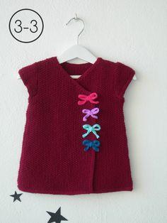 Vestido para bebe hecho a punto de arroz manga corta con lacitos en cadeneta de ganchillo. Disponible en color arena, melocotón y granate.