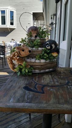 Wildlife diaper cake made with unbleached diapers, burlap ribbon, grapevine, silk leaves and hand puppets.