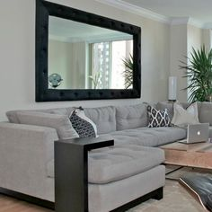 Sectional is from ABC Home, and retractable coffee table is from reclaimed wood with metal legs. Has an adjustable surface for laptop use and dining in front of TV.