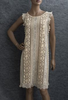 Embroidered tulle/Irish crochet flapper dress, c.1926. Embellished with raised floral embroidery, narrow tucks, decorative crocheted ball buttons on the sides, and bands of pale beige Irish crochet lace. Fluttery lace faux sleeves. The dress slips on without closures.