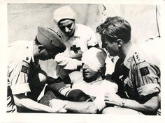 1943-  Italian Red Cross nurse aids two British surgeons, Major G.A. Fowler and Capt. J.S. Hutchinson, in dressing the wounds of an English soldier in Rammacca, Sicily.