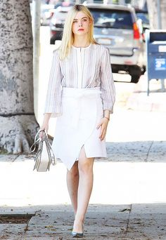 Elle Fanning wears a striped tunic tucked into a white wrap skirt with metallic pumps and a white bag