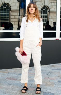Alexa Chung in a white button-down blouse, white overalls, and Birkenstock sandals