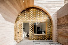 SCREEN: An Old Cave Dwelling in Central China Is Transformed Into a Stylish Home - Photo 6 of 26 - The main entrance of the cave was transformed into a wooden grid façade with a glass curtain wall, allowing ample natural light to enter the space.