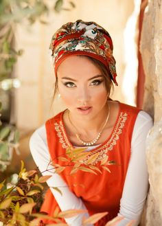 Pre-sewn turban with a large bow at the front! This gorgeous turban is made of a combination of deep orange and white patterned fabrics. The turban is intricately sewn to create the shape of a turban- all you need to do is place it on your head and tie! T