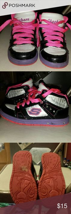 Girls High Top Sketches Toddlers size 12. These sneakers are in good condition no holes or stains rubber sole and shoe laces are in good condition. They are black pink silver and pink with 3 square studs on each sneacker, laces are fat and hot pink, they could use a cleaning but wiping them down is fine as well. There is a sticker stuck to bottom of shoe, it's the price sticker, couldn't peal it off . Tongue on sneaker is white with Sketches written in purple. They  Def have a lot of wear…