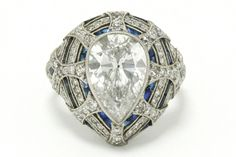 The Beaumont estate 3 carat pear cut diamond engagement ring boasts a sizable sizzler parked right in the middle of a highly detailed French Art Deco style bombe' setting embraced with lush calibre' blue sapphires woven throughout. #diamond #engagementring #love #ido #sapphire #engagementrings #cocktailring #statementring #artdeco #engaged #artdecoring #artdecorings #pearcut #peardiamond #peardiamonds #3carat #diamonds #platinum #estatejewelry #estatejewelery #vintagering #vintagerings Estate Engagement Ring, Antique Engagement Rings, Diamond Engagement Rings, Estate Jewelery, French Art Deco, Pear Diamond, Hand Jewelry, Art Deco Ring, European Cut Diamonds