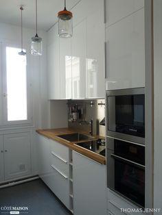Une petite cuisine fonctionnelle - avec des placards laqués tout en hauteur - qui mixe inox, carreaux de ciment pour donner à la fois du charme et de la modernité à la cuisine.