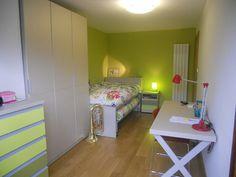 Habitación juvenil de Nora. Compuesta por una mesilla, doble cama y cajonero debajo. Armario sinfonier con frentes de colores verdes y mesa de estudio.