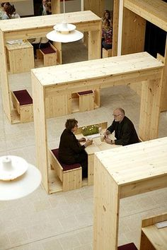 A restaurant with softwood booths that resemble a pair of high-backed meeting chairs, I thought.