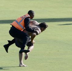A stadium security person tries to stop a man running on the pitch during the third day of the third Test match between South Africa and Pakistan on February 24, 2013 at Super Sport Park in Centurion.