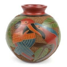 This decorative vase from Nicaragua is 6 inches tall and 5.5 inches in diameter, featuring a colorful double parrot design. This is low fired and not designed to hold water.
