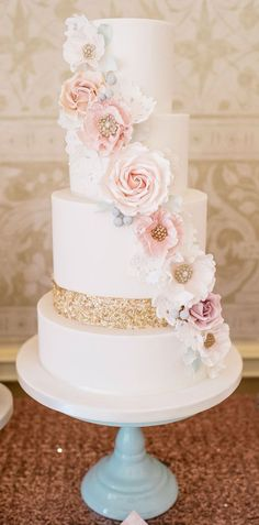 wedding cakes with blush cascading flowers and gold sequins