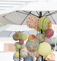 A mix of patterned lanterns hung under an umbrella for a party!