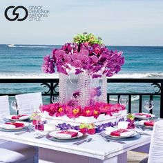 Love the contrast of bright pink and purple flowers on a white table with the blue ocean in the background ~ https://www.weddingstylemagazine.com/travel/hotels/eau-palm-beach-resort-spa