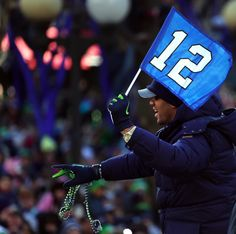 Quarterback Russell Wilson waves a 12th Man flag as the parade goes down 4th Ave.