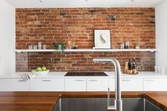 To add storage in the narrow space, Greenawalt used a row of inexpensive Ikea Veddinge cabinets in stark white to frame the original exposed brick wall. He extended the clean, modern lines with minimal appliances, including a recessed sink and a Bosch 30-Inch Induction Cooktop.